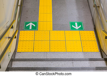 Walkway with direction arrow and disabilities people yellow pavement in Japan subway