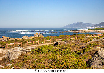 Walkway with fence along Atlantic Ocean coast with mountain on background. Portugal nature. Moss and grass on rocks at seaside.