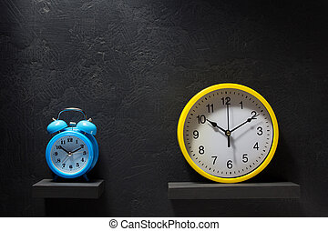 wall and alarm clock at black background texture