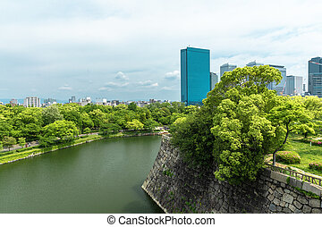 Wall and moat around Osaka Castle and skyscrapers of Osaka Busin