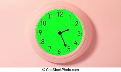 Wall clock with arrows in timelapse on a green background for the chroma key.