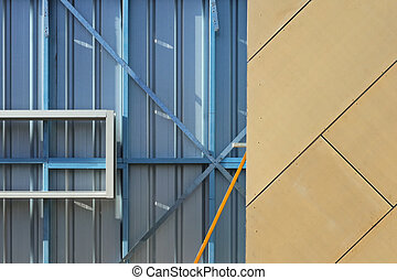Decorative orange facing panels on blue metal frame, wall of incomplete constructed house