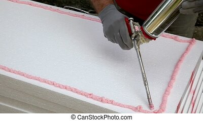 Wall insulation - Worker applying polyurethane expanding...