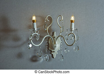 Wall light of gilded metal with two electric candles . vintage wall lamp isolated on white with clipping path . Stylish lamp on the wallpaper .