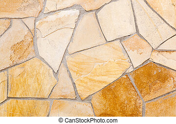 Wall lined with light yellow porphyry stones