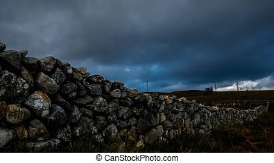 Wall made of rocks on a rural scene with wind turbines on...