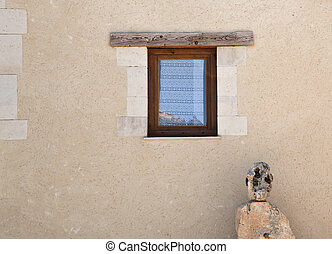 wall of a house with windows and stone sculpture