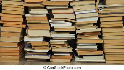 Many books in a pile, pushing in