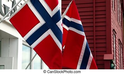 Wall of building with two flags of Norway which flutter in...