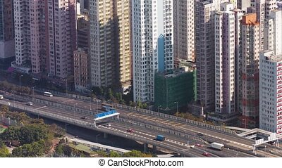Dense wall of highrise buildings demarks the city limits of Hong Kong's urban jungle, with moderate traffic running continuously on a multilevel highway system.