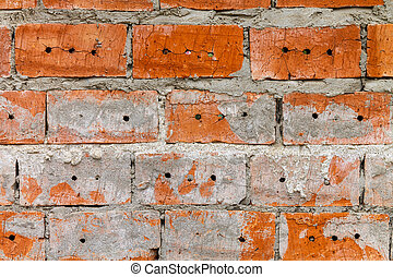 Wall of red brick with holes and gray cement.