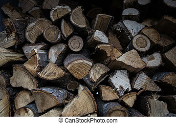 Wall of stacked wood logs as background dark shadows