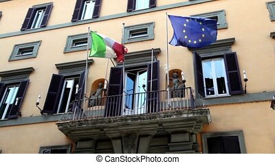 Wall of the building with balcony it is fitted flags of Italy and the EU