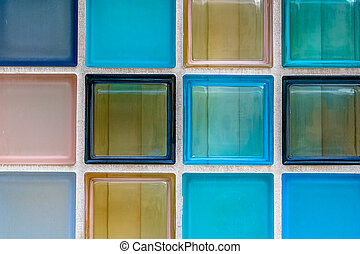 Wall of transparant glass tiles serving as colorful window...