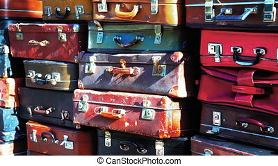 Wall of vintage different types of weathered leather suitcases on top of each other. Colored footage. Prores 422.