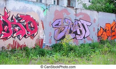 Wall painted with graffiti. The residential area of the industrial city. Graffiti on the walls