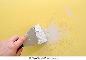 Wall repair - Hand with putty knife repair damaged wall