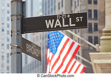 Wall Street sign near Stock Exchange with US flags in New York
