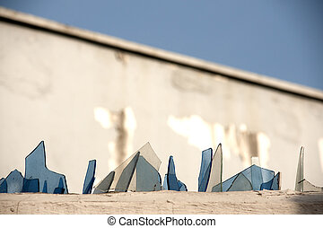 Wall with broken glass - Broken glass on  top of a wall