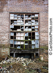 Wall with the broken window of abandoned factory as a background