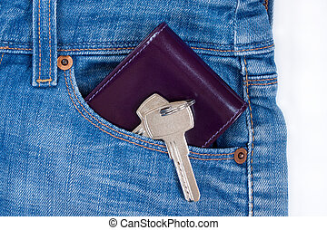 Wallet and keys to the house on a keychain are lying in a side pocket of blue jeans.