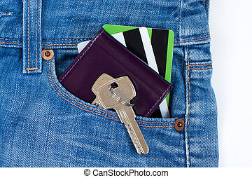 Wallet, credit cards and keys to the house on a keychain are lying in a side pocket of blue jeans.
