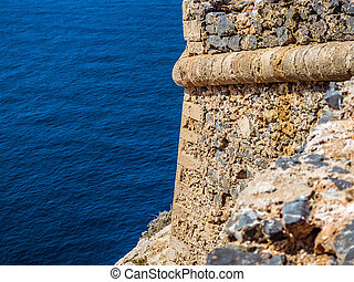 Walls of ancient fortress tower over the blue sea