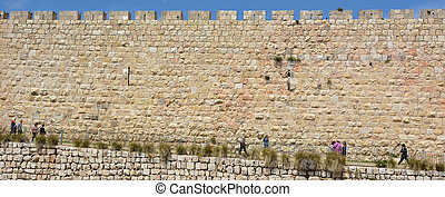 JERUSALEM - MAY 05 2015:Visitors under the Walls of Jerusalem old city, Israel. The wall length is 4km (2.5mi), with average height of 12 meters (39.37 feet) contain 34 watchtowers and 8 gates.