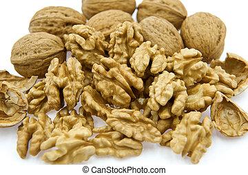 Walnut kernels beside walnuts in shell