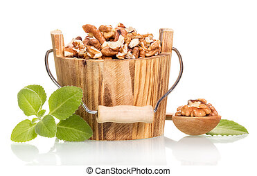 Walnut kernels in wooden bucket and spoon isolated on white.