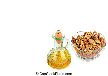 Walnut oil in a glass transparent bottle, walnuts close up isolated on white background. Free space for text.