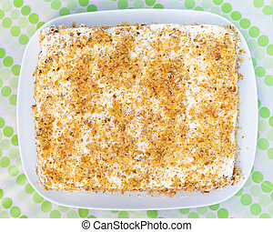 walnuts and cream cake on a plate, top view