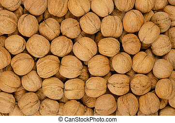 Walnuts background, pile of unshelled nuts