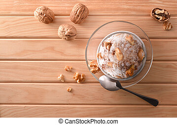 Walnuts ice cream cup decorated with pieces of nuts top