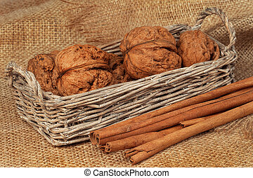 Walnuts in a wicker basket and cinnamon on sacking