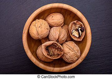 Walnuts in a wooden cup on a black stone board background, frame space for text