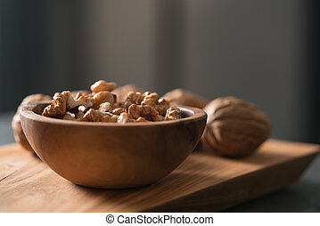 Walnuts in wooden bowl on olive board