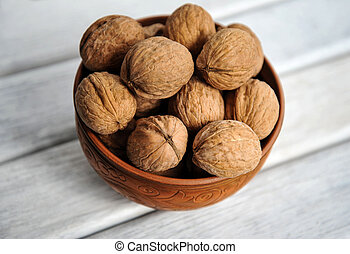 walnuts, nuts in pottery on a white table. view from above
