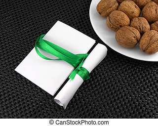 Walnuts on a white plate with invitation card