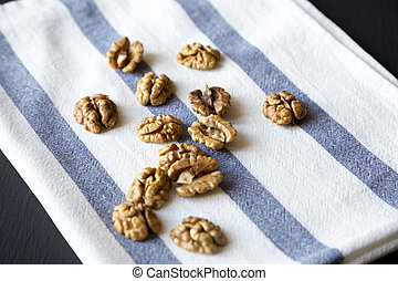 Walnuts on cloth over dark background, side view. Closeup.