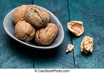 Walnuts on petrol-colored wood in shell