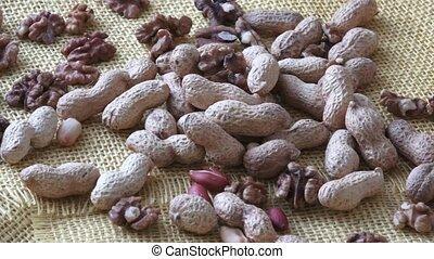 Walnuts, peanuts on yelow background.