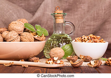 Walnuts, shelled and no, oil bottle closeup on wooden background