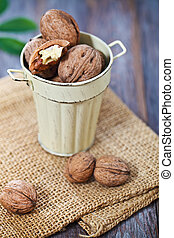 Walnuts with green leaves on the wooden background