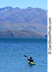 Man rows a kayak in Wanaka lake in the Otago region of the South Island of New Zealand.