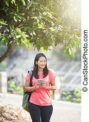 wandelende, buiten, haar, schouwend, jonge, dons, telefoon, terwijl, aziaat, student, activiteit