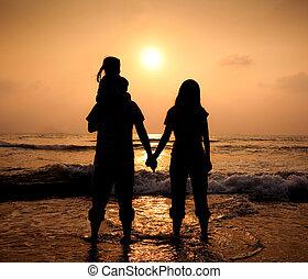 wandelende, silhouette, gezin, terwijl, ondergaande zon , aziaat, holdingshanden, strand, hartelijk