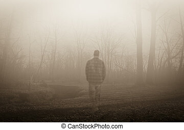 A male ghost wanders through the foggy woods traveling along side a small river; horizontal format, sepia color tone