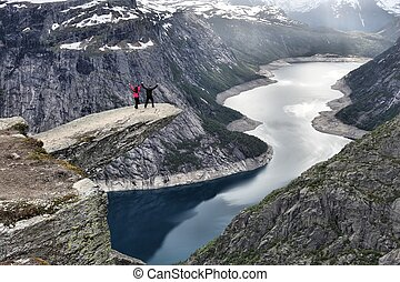 Tourists visit Troll's Tongue in Norway. Tourist attraction known as Trolltunga. Rock pulpit over lake.