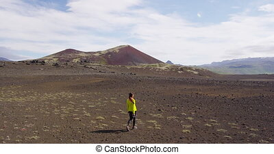 Woman traveler on Iceland walking with camera in the highlands of Iceland